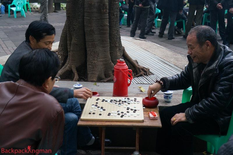 Men play a board game in a park in Chongqing, China.