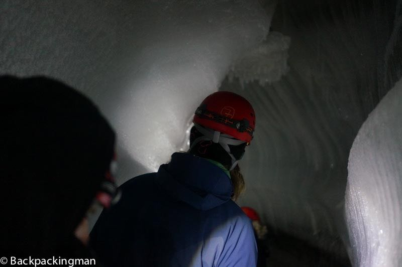 Walking through ice cave in Svalbard
