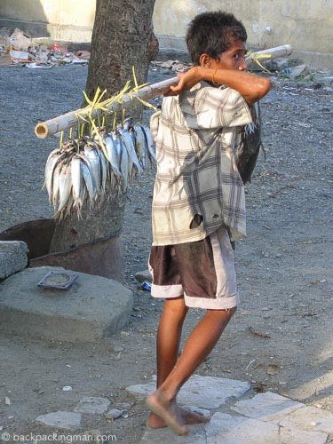 Boy carries fish to market in Dili.