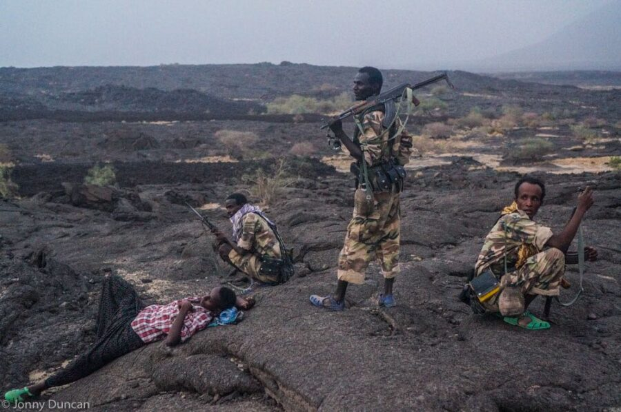 Soldiers and guide taking a rest on the old lava field during the hike down.