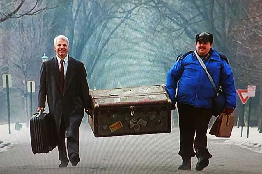 2 men carrying luggage