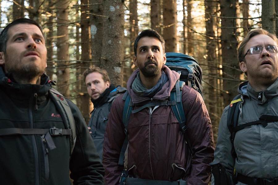 men backpacking in forest